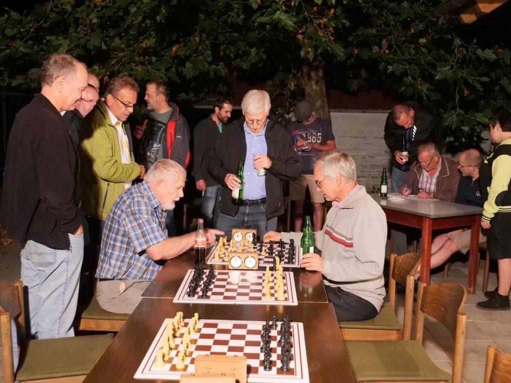 Flutlicht-Atmosphäre. Die letzte Turnier-Partie ist beendet und wird von Spielern und Kiebitzen analysiert. Im Hintergrund zähltTurnierleiter Jürgen Kockel die Punkte zusammen.